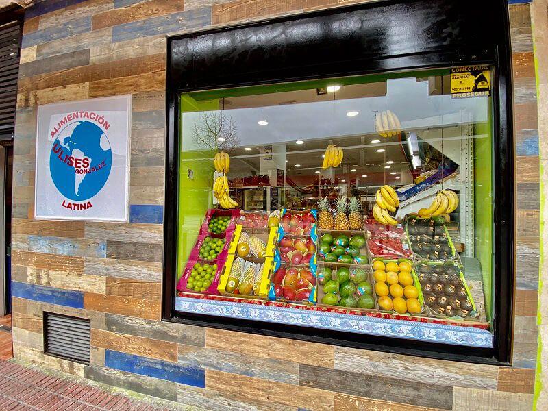 Entrada Tienda Alimentacion Latina Ulises Gonzalez en Mostoles. Escaparate con frutas tropicales (mango, papaya, aguacate, platanos)