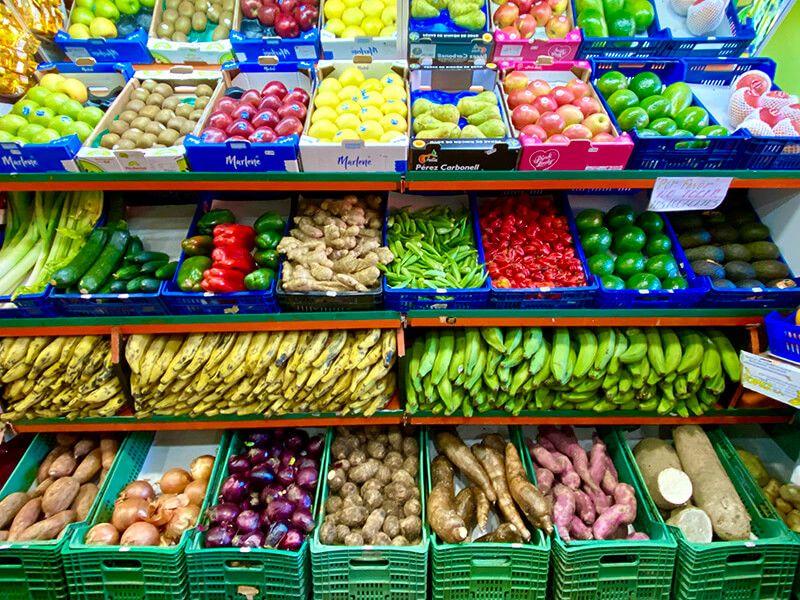 Mostrador con diversas frutas y verduras (cebollas, patatas, yuca, calabacin, jengibre, aguacate)